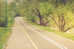 det asfalterade cykelspåret i parkerar längs sjön/det asfalterade cykelspåret i parkerar längs sjön i sanrise royaltyfria foton