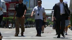 Det asiatiska affärsfolket och turister går över gatan i den Taipei staden stock video