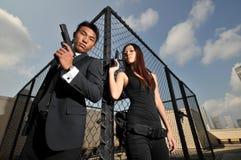 det asiatiska bärande kinesiska paret guns rooftopen royaltyfri bild