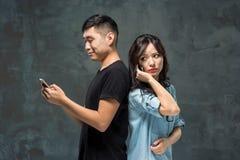 Det asiatiska barnet kopplar ihop genom att använda mobiltelefonen, closeupstående Royaltyfria Foton