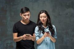 Det asiatiska barnet kopplar ihop genom att använda mobiltelefonen, closeupstående Arkivfoto