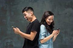 Det asiatiska barnet kopplar ihop genom att använda mobiltelefonen, closeupstående Royaltyfri Bild