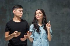 Det asiatiska barnet kopplar ihop genom att använda mobiltelefonen, closeupstående Arkivbild