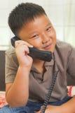 Det asiatiska barnet ser lyckligt på telefonen Royaltyfri Bild