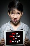 Det asiatiska barnet som rymmer den digitala minnestavlan, med GÖR VI, IT LÄTT! arkivbild