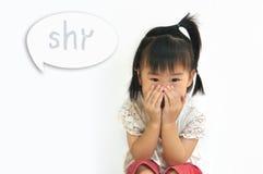 Det asiatiska barnet som täcker henne munnen med henne, räcker fotografering för bildbyråer