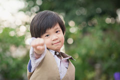 Det asiatiska förtroendebarnet visar hans hand Arkivfoto