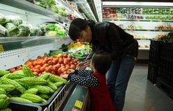 Det asiatiska folket går att shoppa på en supermarket och att välja ny frukt Fotografering för Bildbyråer