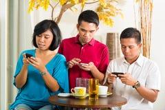 Det asiatiska folket som har gyckel med mobil, ringer Arkivfoton