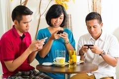 Det asiatiska folket som har gyckel med mobil, ringer Arkivbilder