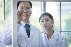 Det asiatiska forskarelaget har att forska i laboratorium royaltyfri bild