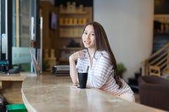 Det asiatiska kafét för sammanträde för kaffe för kvinnadrinkis shoppar Arkivfoto