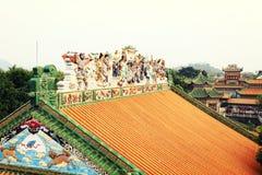 Det asiatiska kinesiska taket av det traditionella huset med guling glasade tegelplattor i klassisk trädgård arkivfoto