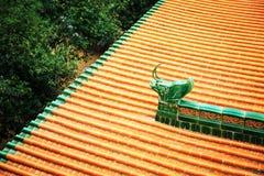 Det asiatiska kinesiska traditionella hustaket med guling glasade tegelplattor i klassisk trädgård Arkivfoton