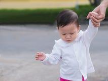 Det asiatiska lilla barnet går parkerar in utomhus- morgonsommar, medan modern Arkivbilder