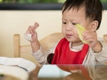 Det asiatiska lilla barnet lär att äta mål själv Fotografering för Bildbyråer