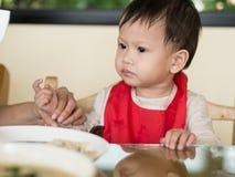 Det asiatiska lilla barnet lär att äta mål själv Arkivbilder