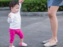 Det asiatiska lilla barnet lär till att gå som är utomhus- Hand för moderhålldaugther Royaltyfri Bild