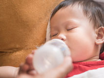 Det asiatiska lilla barnet som äter flaskan av, mjölkar, medan sova Arkivbild