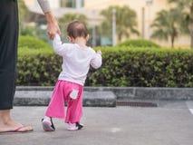 Det asiatiska lilla barnet som går första steg parkerar in, morgon Fotografering för Bildbyråer