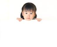 Det asiatiska liten flickanederlag bak vit stiger ombord royaltyfri fotografi