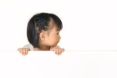 Det asiatiska liten flickanederlag bak vit stiger ombord Fotografering för Bildbyråer