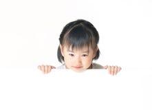 Det asiatiska liten flickanederlag bak vit stiger ombord Arkivfoto