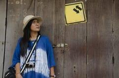 Det asiatiska thai kvinnahandelsresandebesöket och att posera för tar fotoet med retro stil för gammal trädörr Fotografering för Bildbyråer