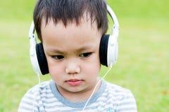 Det asiatiskt behandla som ett barn lyssnande musik för pojke vid headphonen Arkivfoto