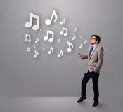 Det attraktiva barn bemannar att sjunga och att lyssna till musik med musikal Fotografering för Bildbyråer