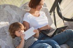 Det attraktiva barnet fostrar genom att använda bärbara datorn, medan dottern som spelar fliken Royaltyfria Foton