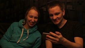 Det attraktiva barnet kopplar ihop genom att använda smartphonen, i kafé och att skratta stock video
