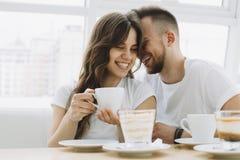 Det attraktiva barnet kopplar ihop på ett datum i ett kafé arkivfoto