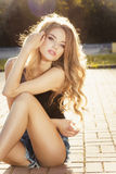 Det attraktiva barnet modellerar med långt blont hår som poserar i strålar av s royaltyfria foton