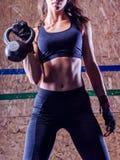 Det attraktiva barnet passade idrottskvinnan som utarbetar, i att lyfta för idrottshall Fotografering för Bildbyråer