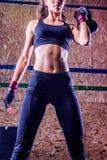 Det attraktiva barnet passade idrottskvinnan som utarbetar, i att lyfta för idrottshall Arkivfoton