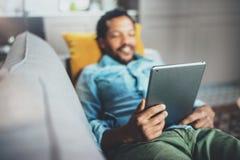 Det attraktiva barnet uppsökte den afrikanska mannen som vilar soffan och använder minnestavlan i modernt hem Begrepp av folk som Royaltyfri Foto