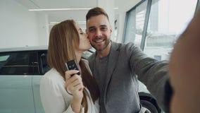 Det attraktiva barnparet tar selfie med biltangenter i modern motorisk visningslokal, når det har köpt den nya bilen De är stock video