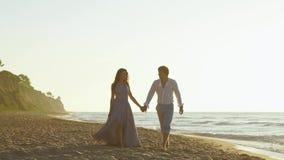 Det attraktiva enloved barnet kopplar ihop att gå på stranden tillsammans Romantiskt bröllopsresabegrepp lager videofilmer