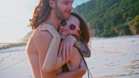 Det attraktiva, förälskade härliga barnet reser par som tycker om solnedgång på stranden som kysser och kramar i ultrarapid Hav lager videofilmer