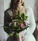Det attraktiva härliga brudinnehavet blommar buketten royaltyfria foton