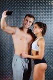 Det attraktiva konditionparet i sportkläder gör selfie inomhus Fotografering för Bildbyråer