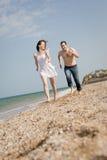 Det attraktiva paret kör längs stranden Fotografering för Bildbyråer