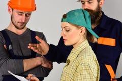 Det bättre planet, bygger bättre Yrkesmässigt folk som arbetar på konstruktionsdesign Män och kvinnabyggmästare som arbetar i lag arkivfoton
