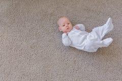 Det barndom-, spädbarn- och folkbegreppet - behandla som ett barn ligger på hans baksida på golvet och att se upp Bakgrund med ko royaltyfri bild