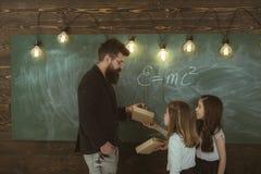Det begåvade barnet behöver vanligt att arbeta som privatlärare åt Det begåvade skolbarnet gör hans konstläxa i klassrum på skola royaltyfri fotografi