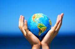 det begreppsmässiga jordjordklotet hands bild Arkivbild