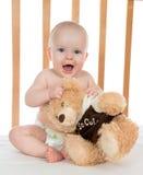 Det begynnande barnet behandla som ett barn flickan som ropar i blöja med nallebjörnen Arkivbilder