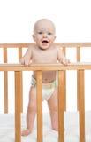 Det begynnande barnet behandla som ett barn pojken som ropar i blöja i träsäng Royaltyfri Bild