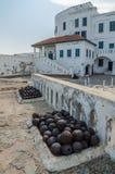 Det berömda slav- handelfortet av den koloniala slotten för tiduddekusten med gamla kanoner och vit tvättade väggar, Ghana, Afrik royaltyfri fotografi